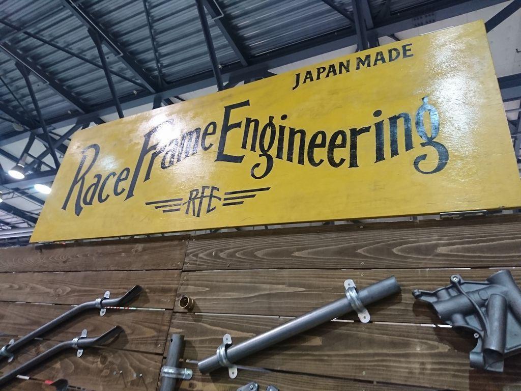 レースフレームエンジニアリングのブース看板。黄色い看板をバックに黒い文字でRace frame enginieeringと書かれている。